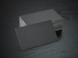 Stack of black blank business cards mockup on black wood table background, - 192694816