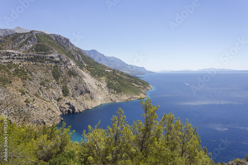 Fototapeta Dalmatian coastline with its cliff and streets through mountains, by the sea