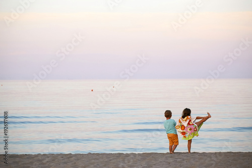 Foto Murales children boy and girl romance on the seashore colorful sunset.