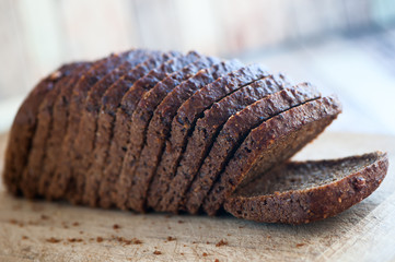 Whole-wheat bread with seeds cut on a wooden board on a natural background. Healthy food, healthy food.