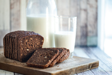 Whole-wheat bread with seeds sliced ​​on a wooden board and milk on a natural background. Healthy food, healthy food.