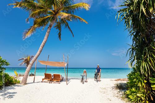 Ojca i córki jazda jechać na rowerze przy tropikalną plażą