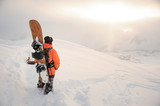 Back view of snowboarder looking on mountain peaks