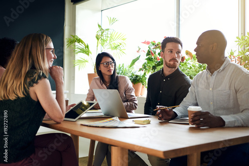 Wall mural Diverse business colleagues having a meeting around a boardroom table