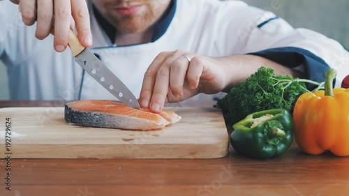 Wall mural Master chef slice fresh salmon on wooden board.
