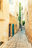 Beautiful narrow street with paving stones in the old city in summer - 192734449