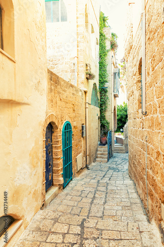 Fototapeta Beautiful narrow street with paving stones in the old city in summer