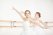 Two little girls outstretching arms while training in ballet class - 192735475