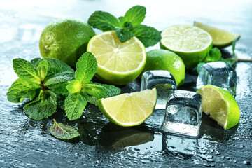Mint, lime, ice ingredients with water drops on slate