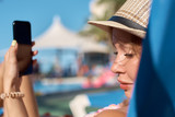 Young girl is laying on a sunbed and holding mobile phone in her hand. - 192744207
