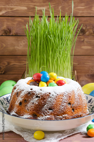 Easter cupcake with powdered sugar and pastry on wooden rustic background