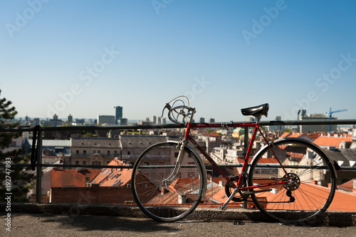 Plexiglas Fiets Vintage red city bicycle locked to the metal fence with view over Zagreb. Old red road bicycle.