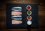 Fresh raw herrings with herbs served on black stone on wooden table - 192749253