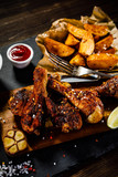 Grilled drumsticks with baked potatoes on wooden background - 192749659