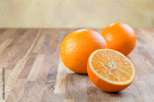 juicy ripe oranges lying on the oak surface of the table