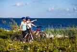 Women riding bicycles at seaside - 192749801