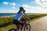 Women riding bicycles at seaside - 192749807