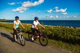 Women riding bicycles at seaside - 192749819
