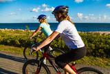 Women riding bicycles at seaside - 192749821
