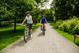 Healthy lifestyle - people riding bicycles in city park - 192749853