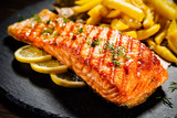 Fried salmon with french fries on wooden table - 192750073