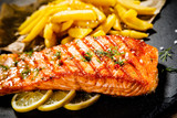 Fried salmon with french fries on wooden table - 192750092