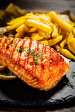 Fried salmon with french fries on wooden table - 192750095