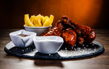 Barbecued drumstick with french fries on wooden table - 192750678