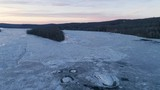 Aerial of lone river island, frozen river, and beautiful sunset lit winter landscape - 192756639