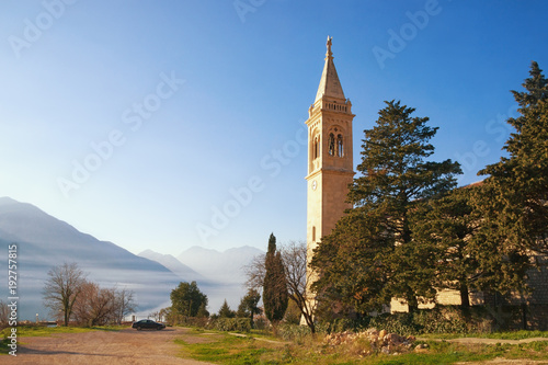 In de dag Blauwe hemel View of Catholic Church of Saint Eustace on coast of Bay of Kotor. Dobrota town, Montenegro, winter. Free space for text