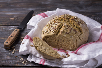 Simple rustic rye oat bread without yeast with seeds on a wooden table, selective focus