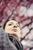 Sad woman lost in thoughts under cherry tree - 192760400