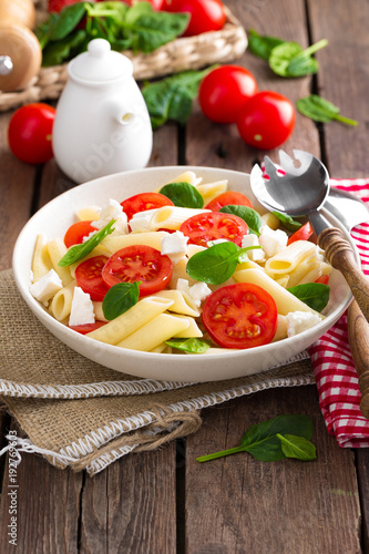 Pasta salad with fresh red cherry tomato and feta cheese. Italian cuisine - 192769603