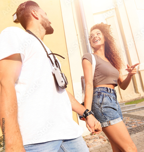 A couple is walking along the streets of the city and having fun
