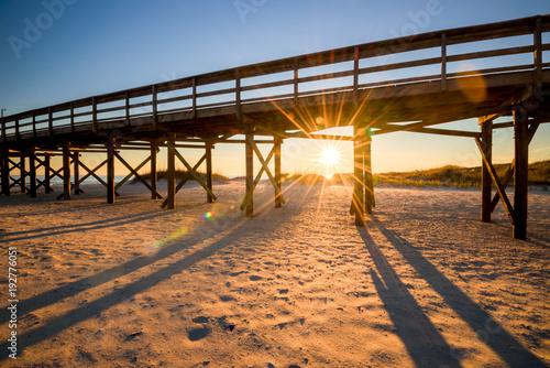 molo na plaży z zachodzącym słońcem pod nim