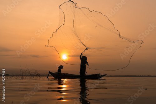 Silhouette of Myanmar fisherman on wooden boat ,Myanmar fisherman in action catc Poster