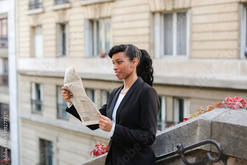 Young mulatto reporter looking at cam with newspaper on balcony near high building. Pretty woman looks successful and has ponytail hairstyle and black fleecy hair. Concept of working correspondent and