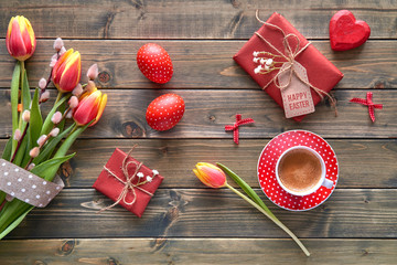 Overhead view of wooden table with springtime decorations, coffee cup, wrapped gifts, flowers and Easter eggs