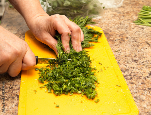 Dill cutting with a knife on the board