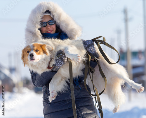A girl is holding a dog in her arms in winter
