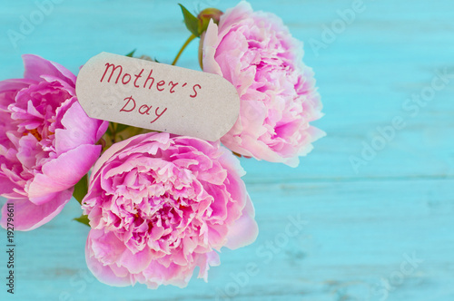 Spring-summer flowers, peonies on a light, wooden background. Greeting card with space for text. Concept for graphic design.