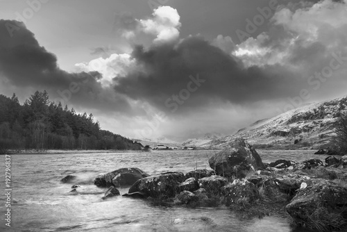 Fotobehang Donkergrijs Beautiful black and white Winter landscape image of Llynnau Mymbyr in Snowdonia National Park with snow capped mountains in background
