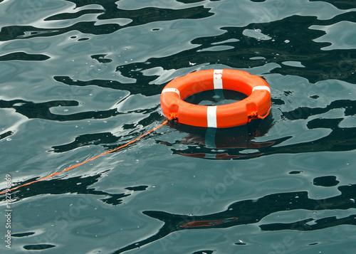 Life ring floating on top of blue ocean water