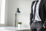Businessman standing waiting in his office - 192797417