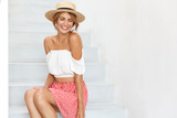Slim happy woman in summer clothing, looks shy down, poses at camera at white stairs for fashionable magazine, with copy space for your promotional text or advertisment. Beauty, fashion and youth