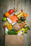 Grocery shopping concept. Balanced diet concept. Fresh foods with shopping bag on rustic wood background - 192802438