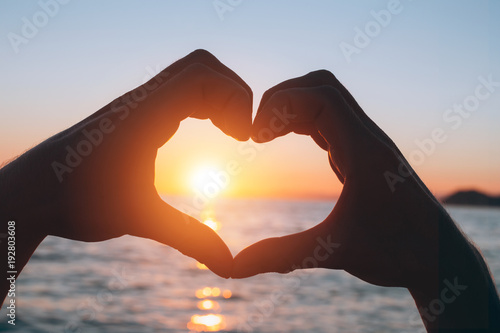 Male hands in a heart shape at sunset