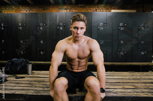 serious fitness model of a bodybuilder male trainer sitting on a bench in the locker room.
