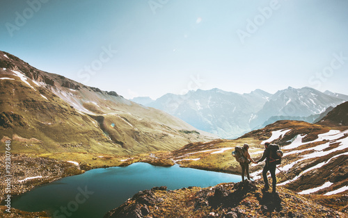 Couple travelers holding hands on mountain cliff over lake together love and Travel Lifestyle wanderlust concept adventure vacations outdoor aerial view.