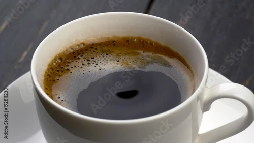 Sticker Drops of coffee are falling into espresso cup. Black wooden background. Slow motion shot